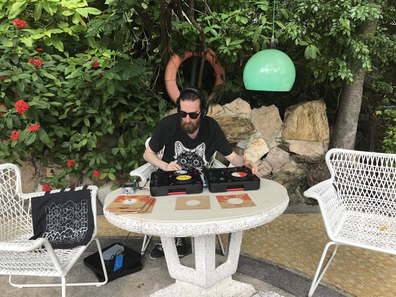 Viktor sätter ihop ett DJ-set med thailänska 7-tummare vid poolen på The Atlanta, med skivor hittade i Bangkok.